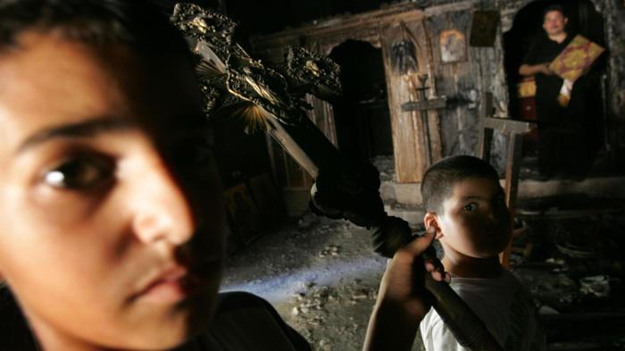 Palästinensische Kinder mit einem verkohlten Kruzifix in einer ausgebrannten Kirche. Aufgebrachte Muslime hatten sie nach islamkritischen Äußerungen des Papstes im Jahr 2006 angezündet Foto: Getty Images