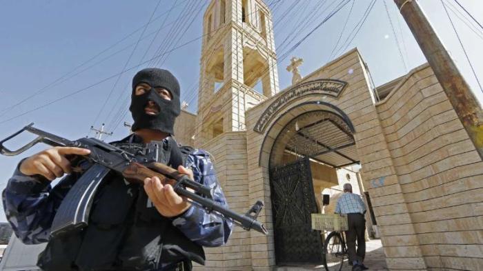 Ein irakischer Sicherheitsmann beschützt eine Kirche nahe der Stadt Mossul vor Übergriffen durch islamistische Milizen